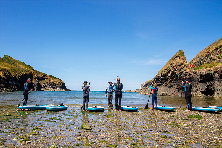 a sand up paddleboard lesson at port gaverne in cornwall with cornish rock tors