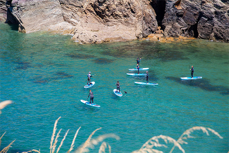 a stand up paddleboarding lesson with cornish rock tors at port gaverne on a summer day
