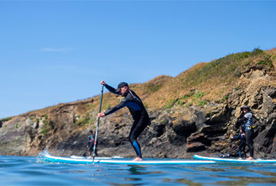 stand up paddleboarding at port gaverne with cornish rock tors