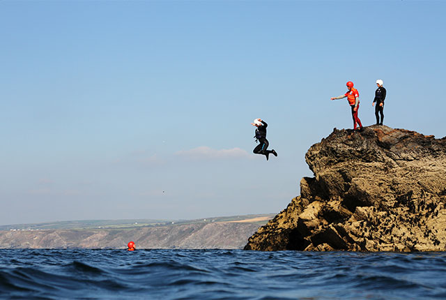 jumping into the sea from the end of castle rock during a coasteering session with cornish rock tors