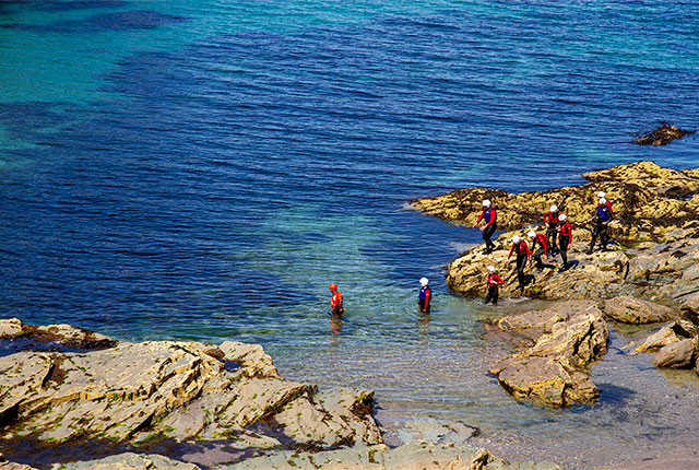 coasteering group wading in the clear shallow water between rocky outcrops
