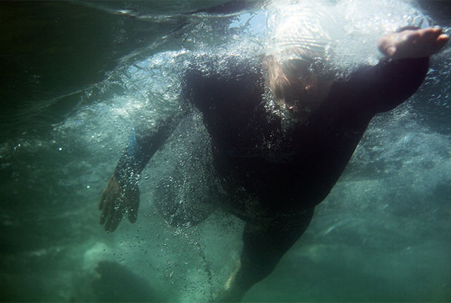 looking up from underwater at a swimmer in the sea