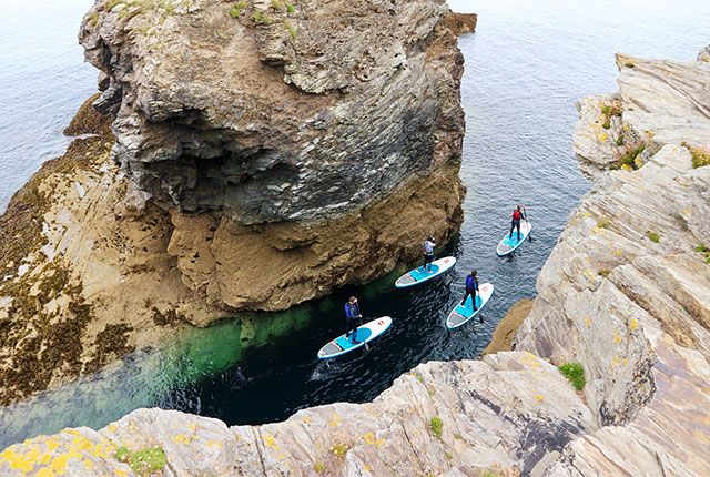 a group paddling through the gut on stand up paddleboards with cornish rock tors