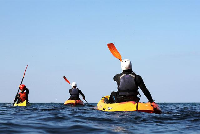 paddling towards the horizon on sea kayaks