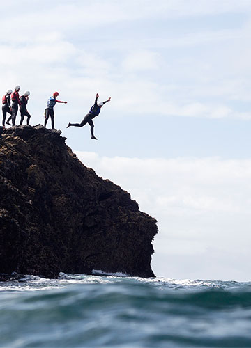 jumping into the sea from the rocks during a coasteering session in cornwall with cornish rock tors