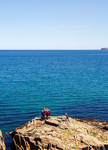 a coasteering group on the rocks above the sea looking across the cornish coast