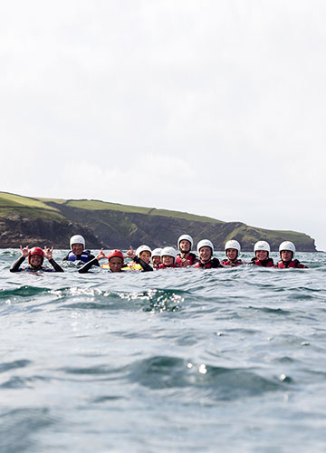 a coasttering group smiling for the camera during a session with cornish rock tors