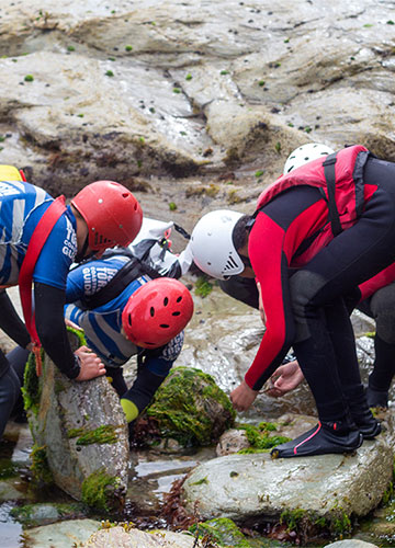 coasteering guides lifting a rock to show clients the marine life in the rock pool beneath it