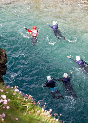 coasteering group swimming in clear water in cornwall