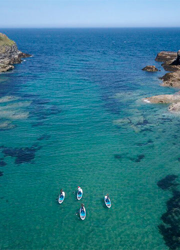 aerial view of a stand up paddleboard lesson and tour setting off from port gaverne in cornwall on a sunny summer day