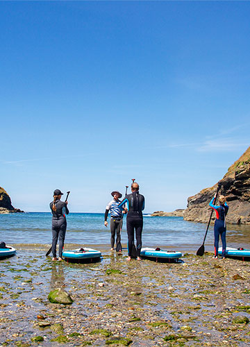 instructor teaching the basics of stand up paddleboarding on the beach before setting off, at cornish rock tors base at port gaverne