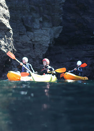 sea kayaking group with guide paddling under cliffs in cornwall