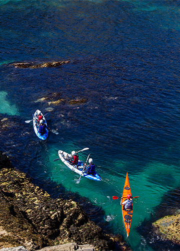 sea kayakers paddling through shallow clear water in cornwall