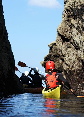 sea kayakers paddling through a gulley