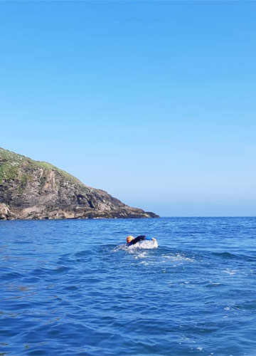 a swimmer setting out from port isaac on a sea swim to port gaverne, cornwall