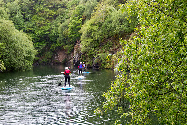 stand-up paddleboarding on a calm inland lake in north cornwall with cornish rock tors