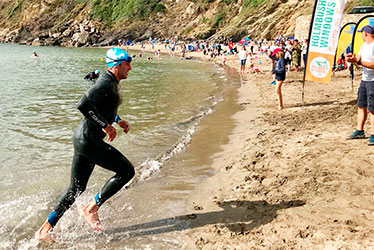 jon waters exiting the sea after the swim leg of a triathlon