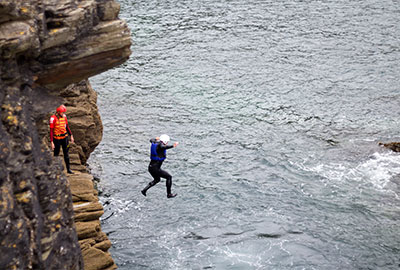 a man jumping from the rocks in to the sea during a coasteering session with cornish rock tors on father's day