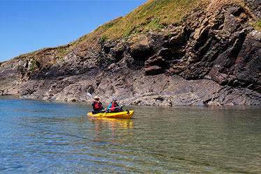 father and child sea kayaking together in cornwall
