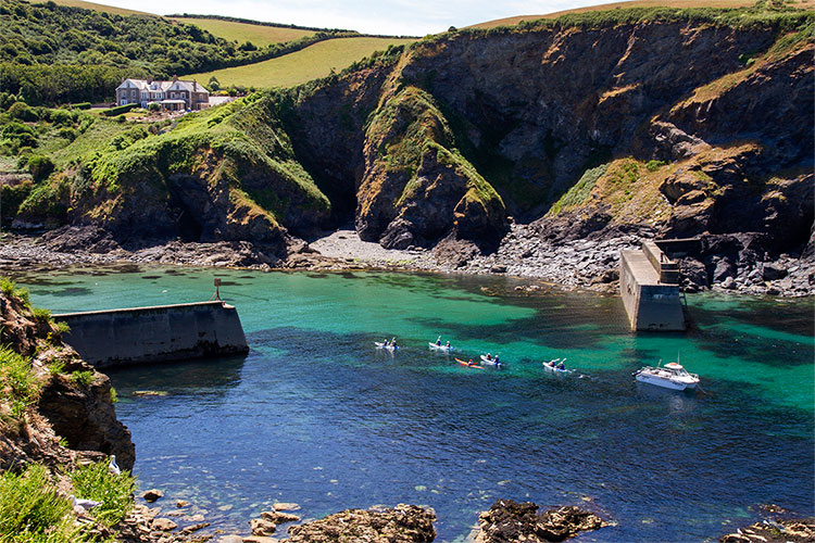 a guided sea kayaking group paddling in to port isaac harbour in north cornwall
