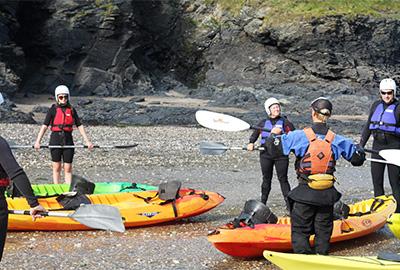 a group learning paddling skills on the beach before a sea kayaking trip