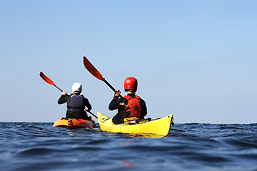 kayaking guide and client paddling at sea