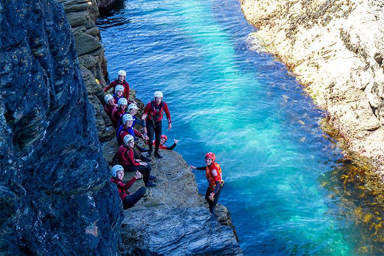 group of teenagers coasteering with cornish rock tors