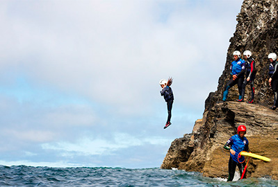 child juming into the sea during a coasteering session with cornish rock tors