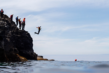teenager jumping into the sea whilst coasteering at port gaverne with cornish rock tors