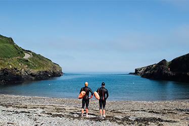 open water swimmers stood on the beach at port gaverne wearing swim research wetsuits