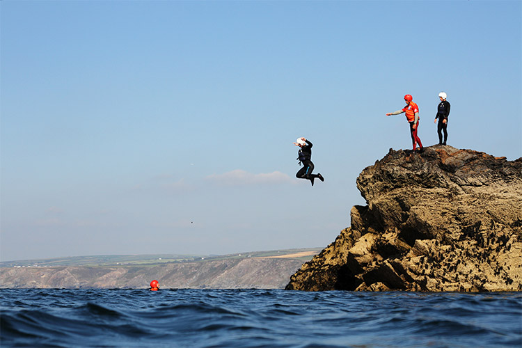 coasteering group jumping into the sea in port gaverne with cornish rock tors