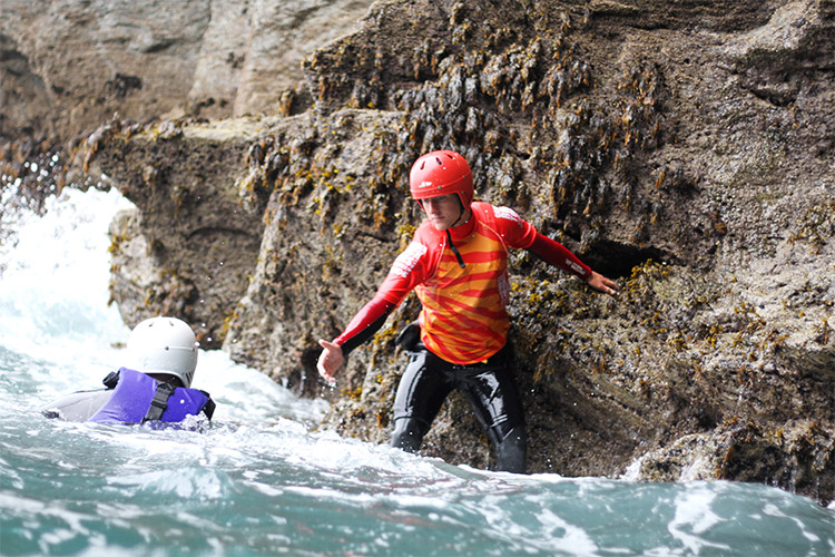 coasteering guide offering a helping hand to a client
