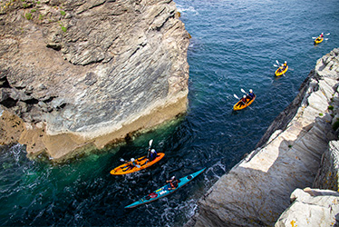 sea kayaking through the gut at port gaverne with cornish rock tors