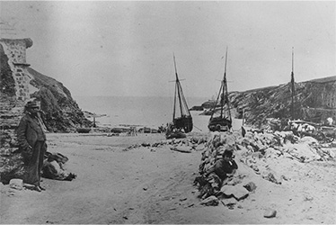 Warwick Guy leaning on Union Cellar, Port Gaverne, with slate boats on the beach in the background, circa 1875, Port Gaverne, Cornwall