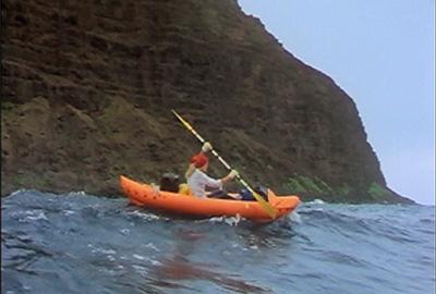 audrey sutherland paddling her inflatable canoe along the coast of molokai